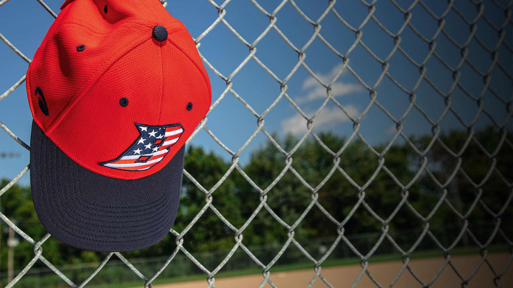Youth Baseball hat hanging on dugout fence