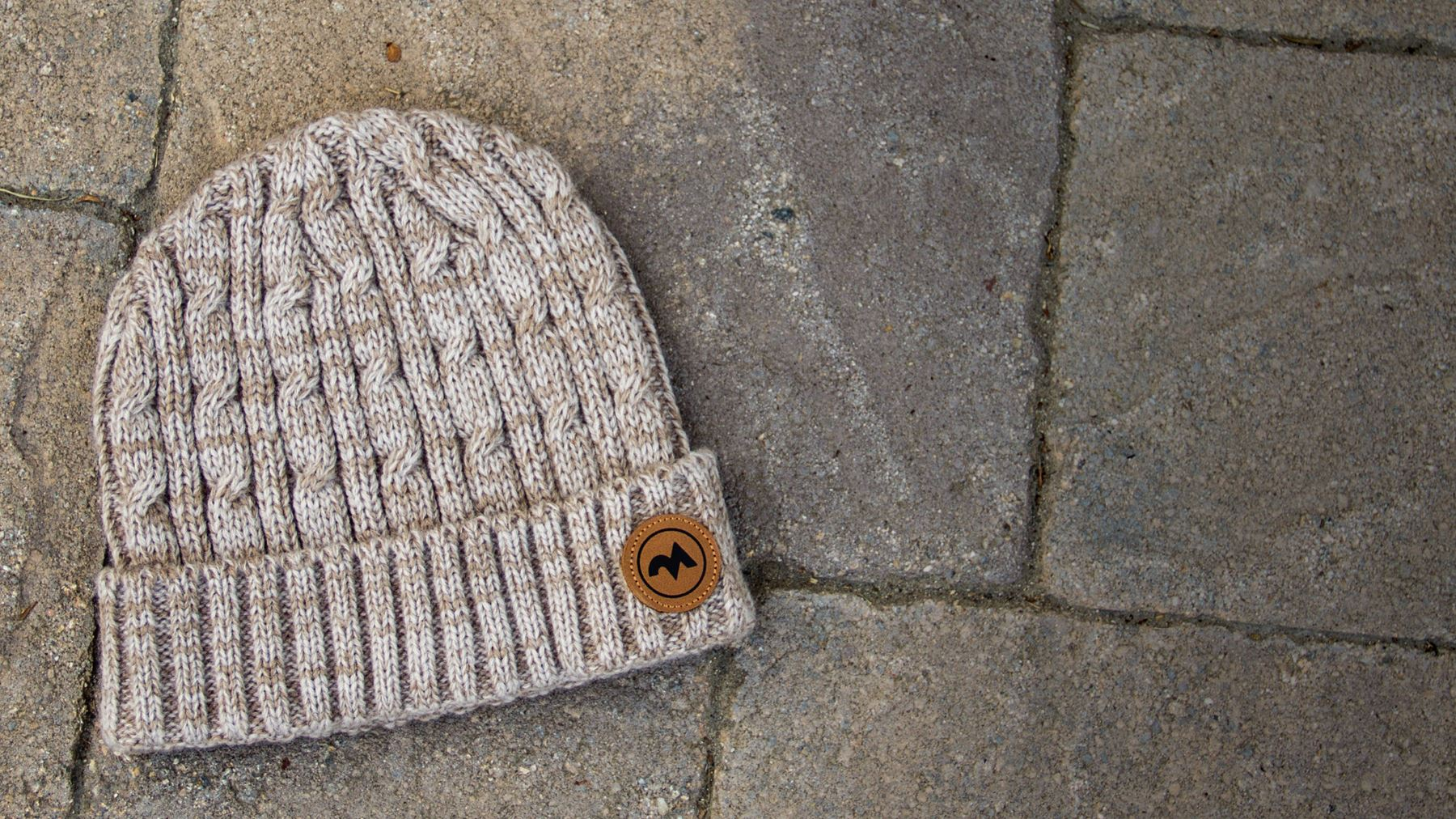 Cuffed Cable Knit hat laying on stone walkway